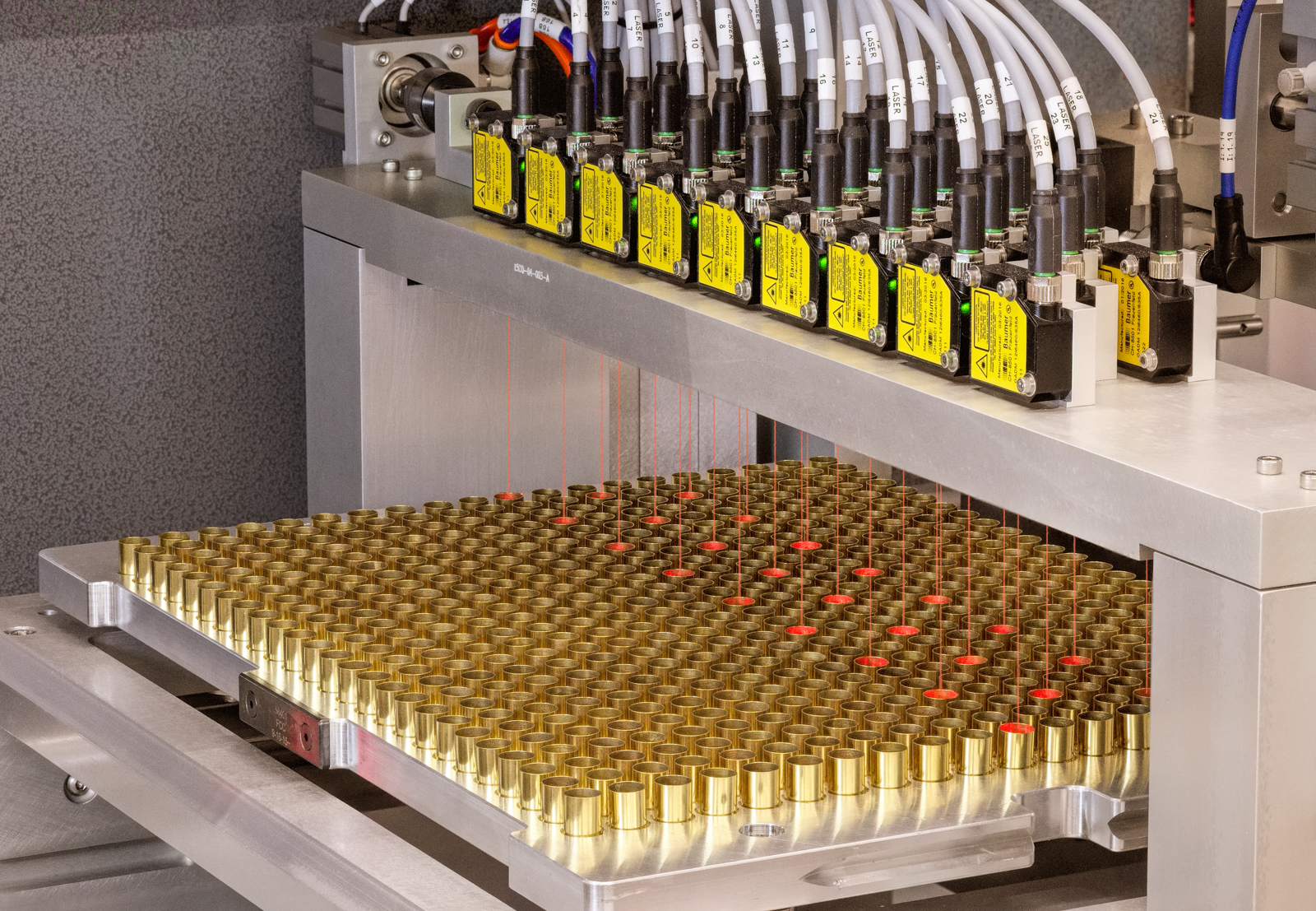 A bank of lasers light up cartridges being manufactured with red.