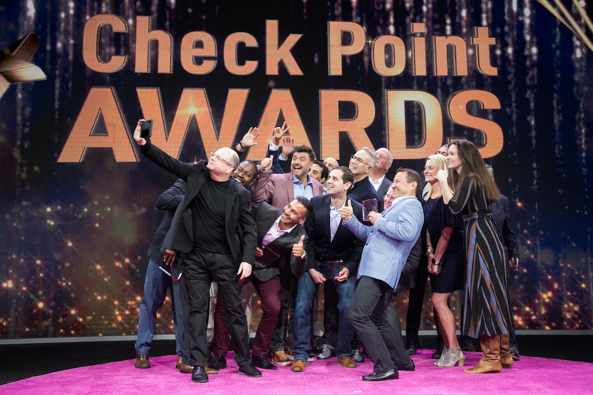 A large group selfie is being taken on a pink carpet during an awards ceremony in New Orleans