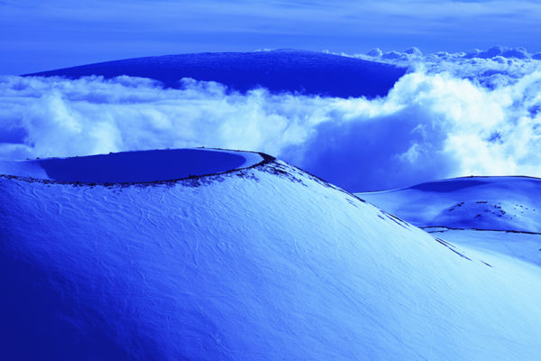 Snow covered cinder cone with Mauna Loa, second highest mountain in Hawaii at 13,679'.