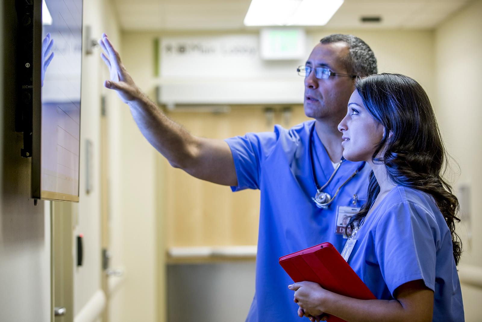 Mixed race medical doctors study charts hallway