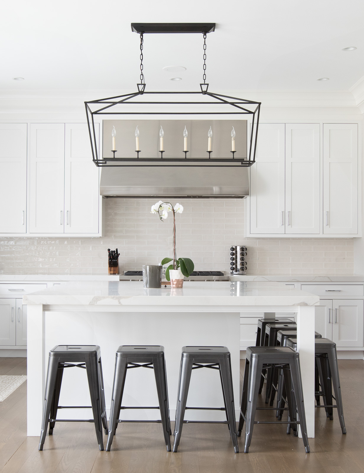 White kitchen with black stools and stainless steel pendant.