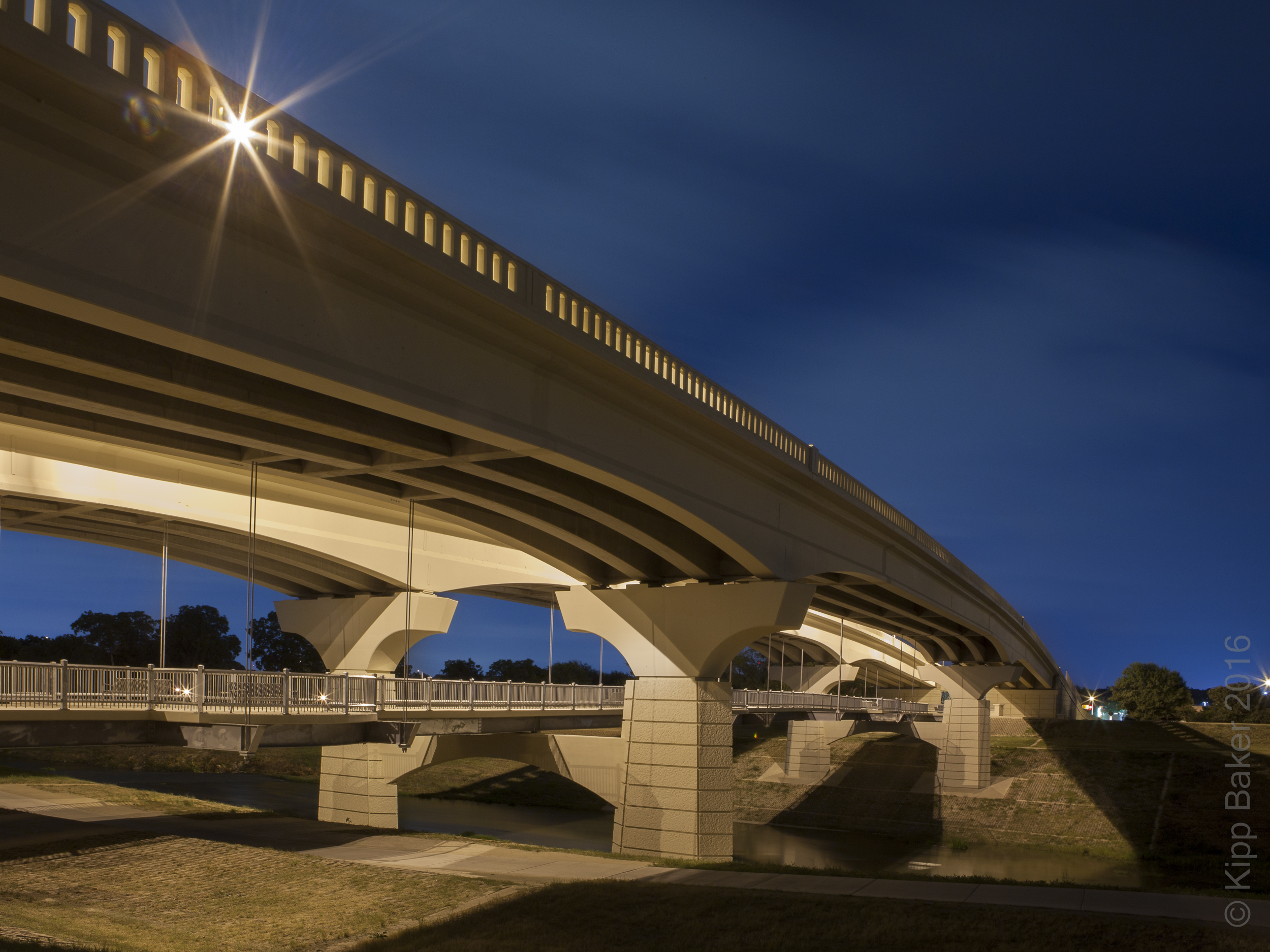 Clearfork Main Street Bridge in Fort Worth, Texas arches from high left to low right at twilight.