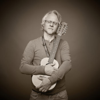 Musician Phil Wisneski cradles his beloved ukulele in his arms, embracing it with his eyes closed.