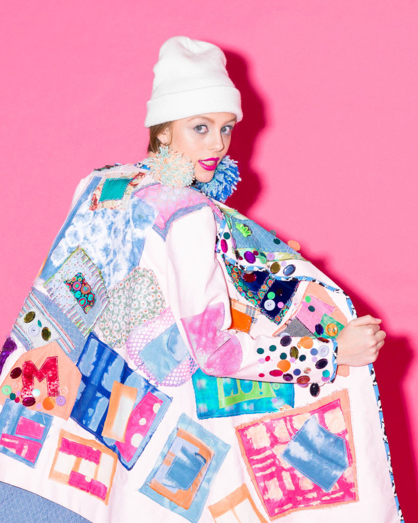 fashion model wearing patchwork trenchcoat, white knit beanie, yarn puff earrings on pink background